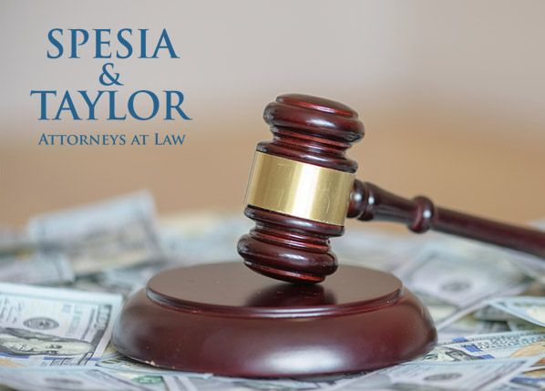 Gavel with money auto accident settlement - Spesia & Taylor